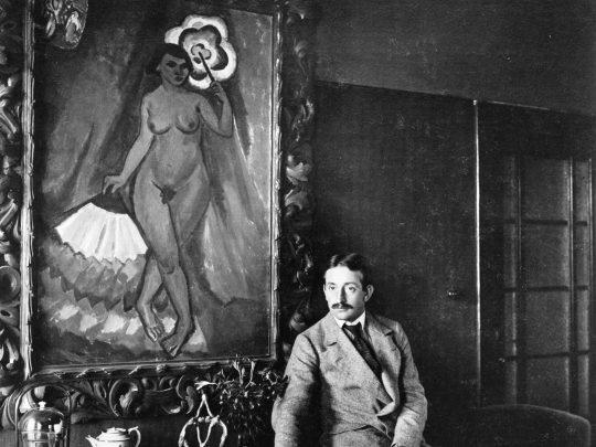"""Max Pechstein vor dem Gemälde """"Akt mit Schirm und Fächer"""", 1912/47, in der Offenbacher Str. 8 im Herbst 1913/14 Fotograf Waldemar Titzenthaler, Max Pechstein. Foto: (c) 2019 Pechstein Hamburg / Tökendorf"""